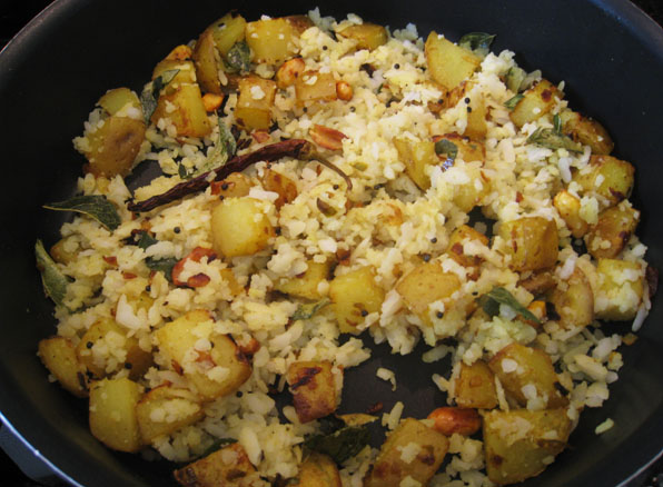 Fluff up Poha with a fork and add it to the pan