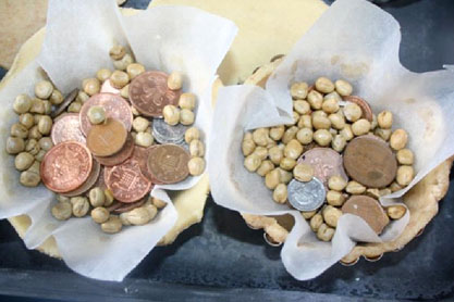 Place beans and coins in the pastry to weigh them down